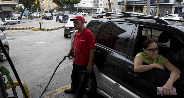 In this March 23, 2017 file photo, an employee pumps gas for a customer at a gas station in Caracas, Venezuela. (AP Photo)