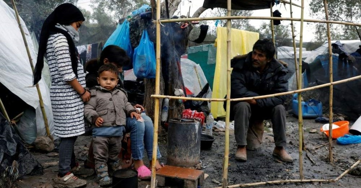 Migrants sit outside their tents at a makeshift camp for refugees and migrants next to the Moria camp, Lesbos, Dec. 13, 2019. (REUTERS Photo)