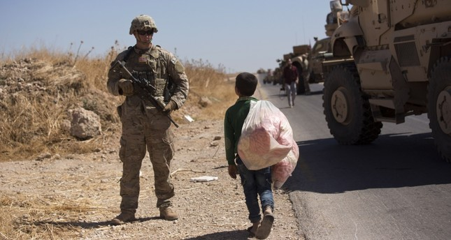 A Syrian boy selling snacks looks at a U.S. soldier standing guard during the first joint ground patrol by American and Turkish forces in the so-called safe zone on the Syrian side of the border with Turkey, Sept. 8, 2019.