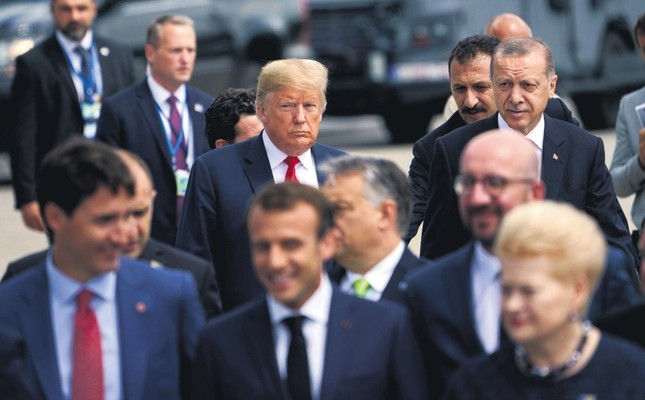 U.S. President Donald Trump (L) and President Recep Tayyip Erdoğan follow other leaders to a family photo during the NATO summit at Brussels, July 11, 2018.