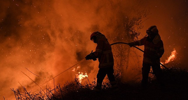Firefighters try to extinguish a fire in Cabanoes near Louzan as wildfires continue to rage in Portugal on October 16, 2017. (AFP Photo)