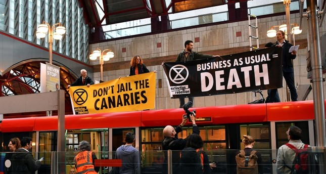 Demonstrators stand on top of a DLR train as they block the traffic at Canary Wharf Station, during the Extinction Rebellion protest in London, Britain April 25, 2019. (REUTERS Photo)