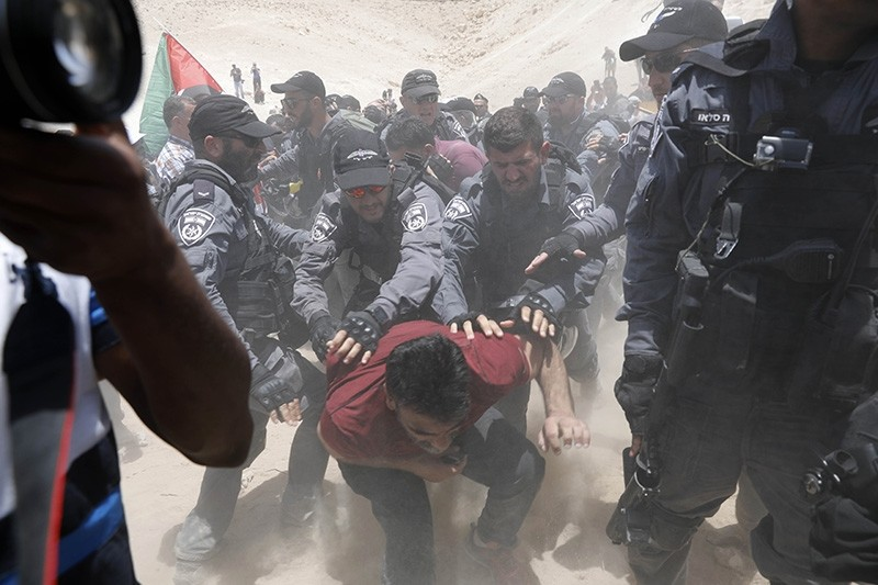 Palestinian demonstrators clash with Israeli policemen as they try to prevent an Israeli tractor from entering the Bedouin community of Khan al-Ahmar on July 4, 2018. (EPA Photo)
