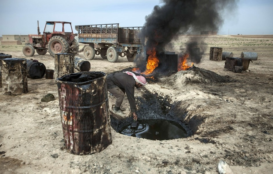 A picture taken on April 15, 2013 shows a Syrian man in the Al Raqqa countryside, pouring crude oil brought from Deir el-Zour into a pit where it will be distilled as part of the refining process. (AFP Photo)