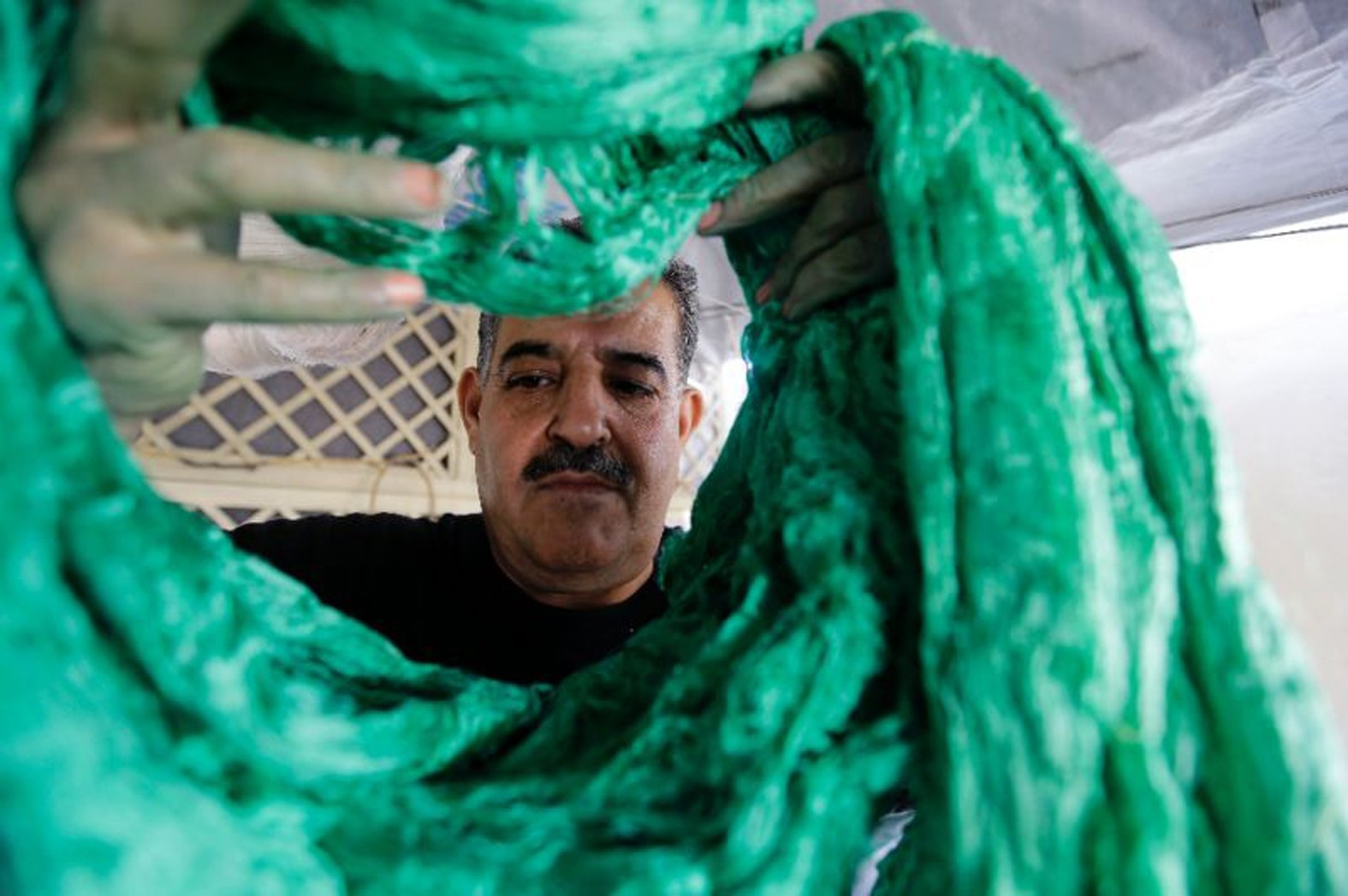 Mohammad al-Rihawi sometimes works just one day a week at his silk dyeing workshop because of low demand.