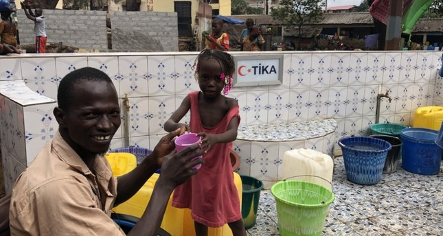 A man helps a girl drink water from a fountain set up by TİKA in Guinea's Conakry where the locals had to walk for kilometers to reach drinkable water.