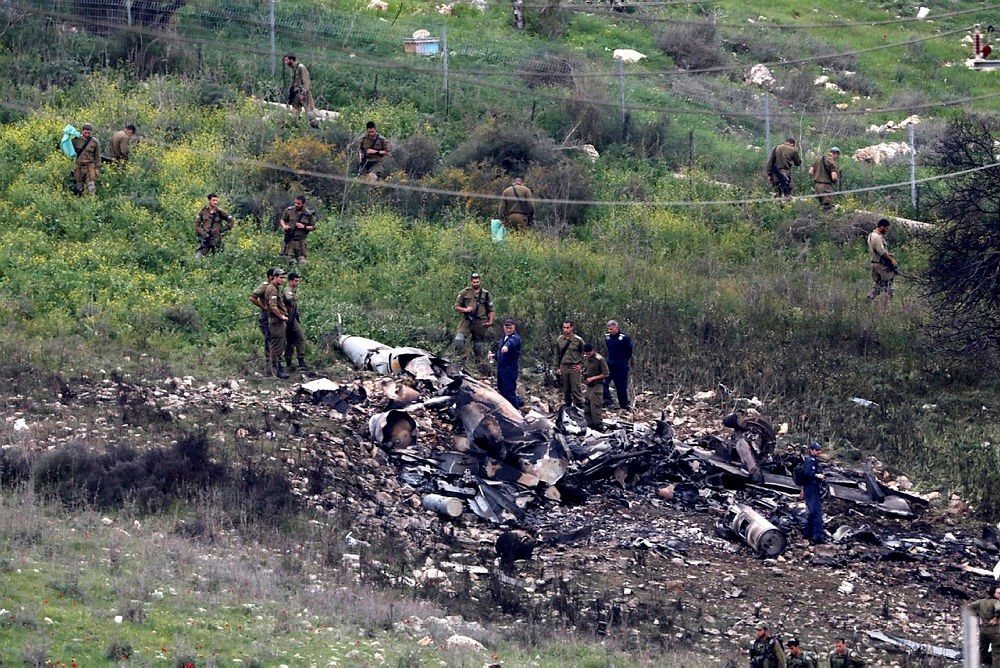 Israeli soldiers inspect the remains of an Israeli F-16 fighter jet that was shot down after a hit by Syrian anti-aircraft system, 10 February 2018. (EPA Photo)