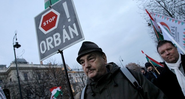 A protester holds a sign reading Stop Orban as members and sympathisers of several trade unions, political parties and civil organisations march in Budapest on December 16, 2018. (AFP Photo)