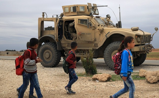 Syrian schoolchildren walk past U.S. troops on patrol close to the Turkish border in al-Hasakah, Nov. 4, 2018.