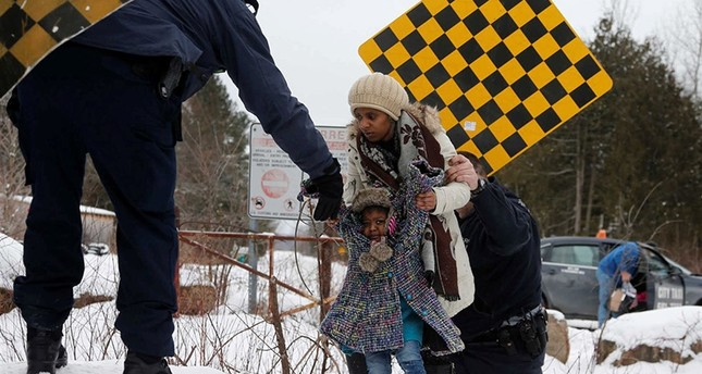 A woman from Sudan is taken into custody by Royal Canadian Mounted Police RCMP officers after arriving by taxi and walking across the U.S.-Canada border into Hemmingford Reuters Photo