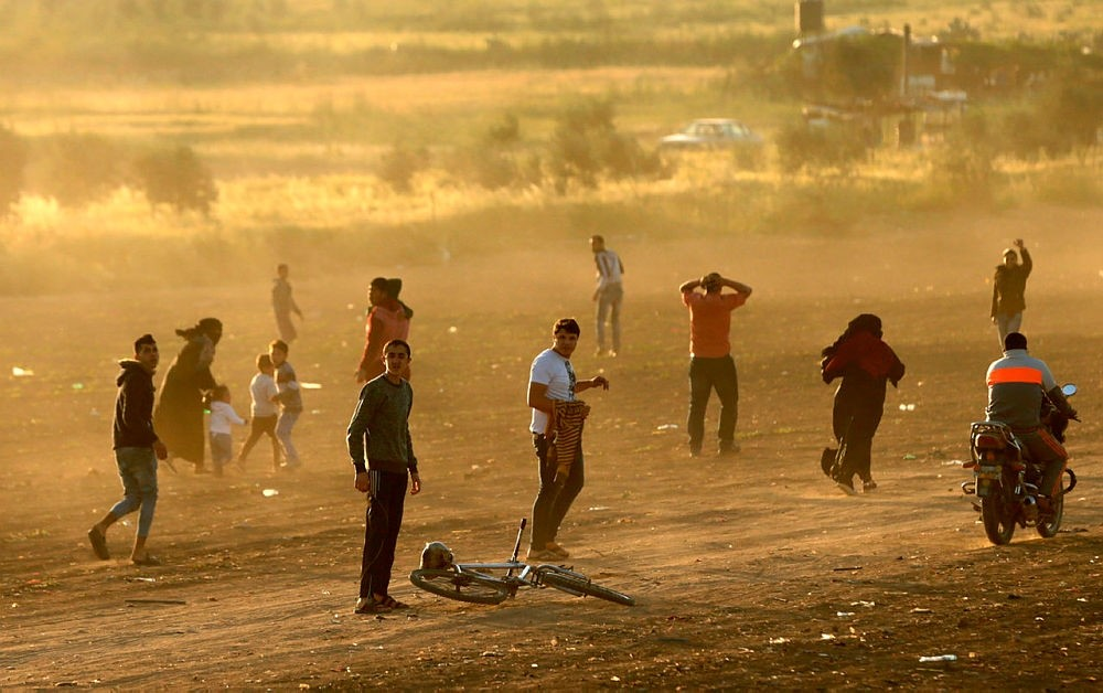 Palestinian protesters run for cover from tear gas fired by Israeli security forces during a protest along the border with Israel, east of Gaza City in the Gaza strip on March 31, 2018. (AFP Photo)