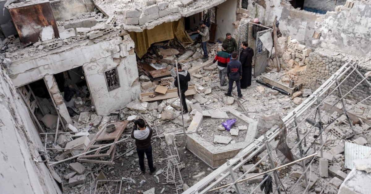 Syrians inspect damage from a reported regime airstrike at a civilian residence in the northern Idlib province, March 10, 2019.