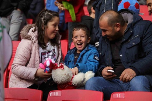 A child laughs after catching a stuffed teddy bear thrown by fans in Samsun, Nov. 24, 2019. (DHA Photo)