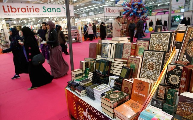 Visitors walking past a bookseller displaying copies of the Quran during the 32nd Annual Meeting of France's Muslims, at Le Bourget Exhibition center, north of Paris, April 3, 2015.
