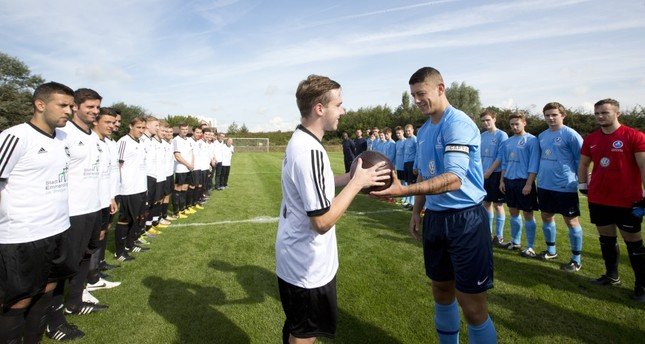The team captains of Britain's Newark Town FC and Germany's FC Emmendingen exchange a football prior to a re-creation of the World War I Christmas Truce football match in Messines, Belgium.