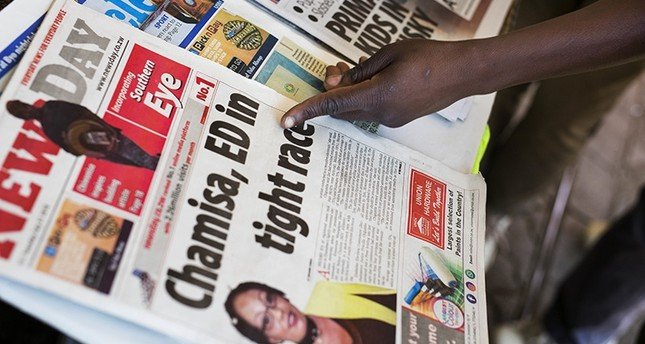 A Zimbabwean man points at a newspaper headline, in Bulawayo, Zimbabwe, Tuesday, July 31, 2018. (AP Photo)
