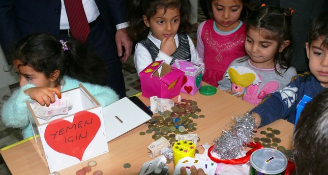 Children in the Yeşilyurt district of Tokat province hand out money they collected from their allowances to officials for the Yemen aid campaign yesterday.