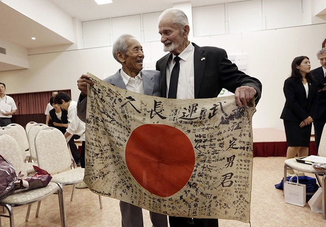 WWII veteran Marvin Strombo (R) and Tatsuya Yasue, 89-year-old farmer, hold a Japanese flag with autographed messages which was owned by his deceased brother Sadao Yasue, during a ceremony in central Japan's Gifu prefecture, Aug. 15, 2017. (AP Photo)