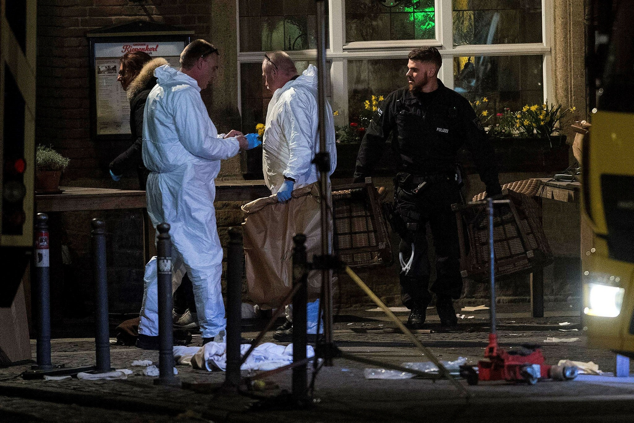 Investigators working at the square where a man rammed his car into a crowd, killing two and injuring several others in Muenster, Germany, April 8.