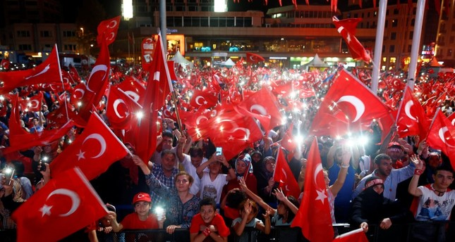 People wave flags as they listen to President Erdoğan on a giant screen in Istanbul's Taksim Square, Aug. 10.