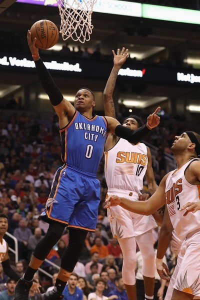 Russell Westbrook of the Oklahoma City Thunder lays up a shot past Derrick Jones Jr. of the Phoenix Suns during the first half of the NBA game at Talking Stick Resort Arena in Phoenix.