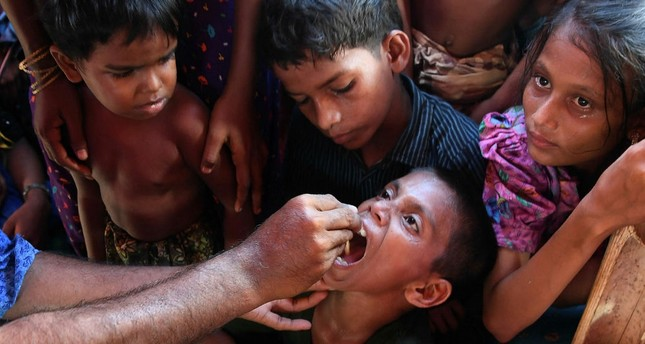 Rohingya refugee children look on as a Bangladeshi volunteer administers an oral cholera vaccine at the Thankhali refugee camp in Ukhia district, Oct. 10.