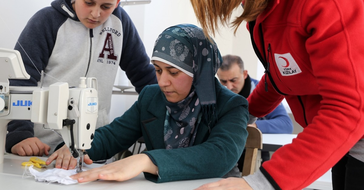 A Red Crescent worker shows a Syrian woman how to sew at a workshop in u0130zmir, Mar. 1, 2019.
