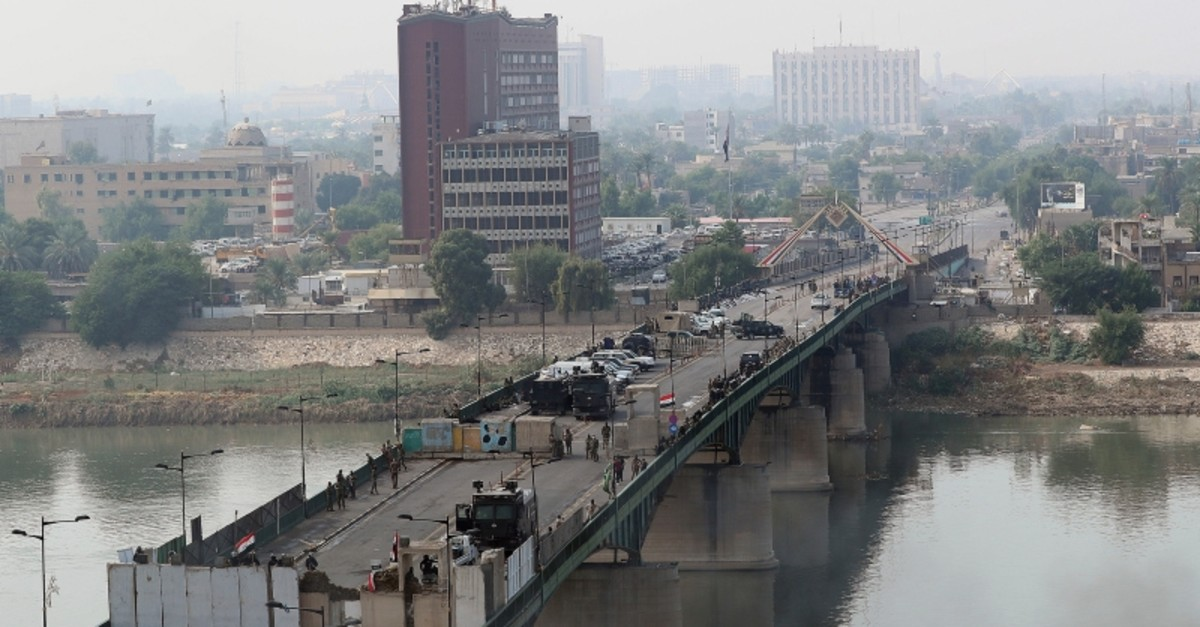 Security forces fire tear gas and close the bridge leading to the Green Zone during a demonstration in Baghdad, Iraq, Wednesday, Oct. 30, 2019. (AP Photo)