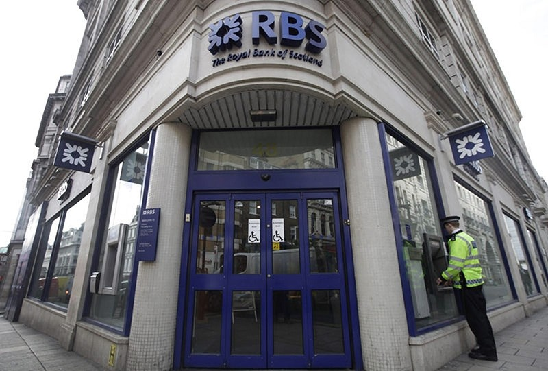 A British police officer uses the cash machine at a Royal Bank of Scotland (RBS) branch in central London (AP File Photo)