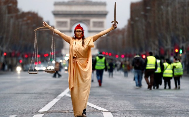 A woman dressed as Marianne, a French symbol of justice, poses during a demonstration by the yellow vests movement at the Champs Elysees near the Arc de Triomphe, Paris, Dec. 22.