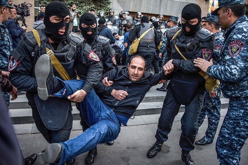 Armenian special police forces detain opposition supporters during their anti-government rally in front of the entrance to government headquarters in central Yerevan (AFP Photo)