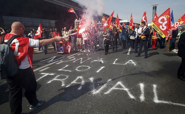 Striking employees hold French CGT labour union flags during a demonstration against the labour reforms law at the Charles de Gaulle Int'l Airport in Roissy, near Paris, France, June 7, 2016. The slogan reads No to the labour law. (Reuters Photo)