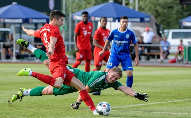 Bayern Munich's Polish forward Robert Lewandowski scores past Rottach-Eger's goalkeeper Domingo Grafunder during the prs-season friendly football match between FC Rottach-Eger and FC Bayern Munich in Rottach-Eger, southern Germany on August 8, 2019.