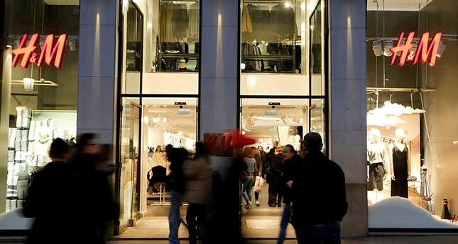 People walk past the windows of an H&M store in Barcelona, Spain, December 30, 2016. (Reutes Photo)