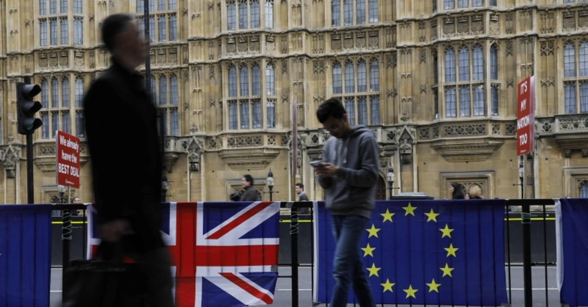 Pedestrians walk past a British national flag (L) and an EU flag outside the Houses of Parliament in central London on March 21, 2019. (AFP Photo)