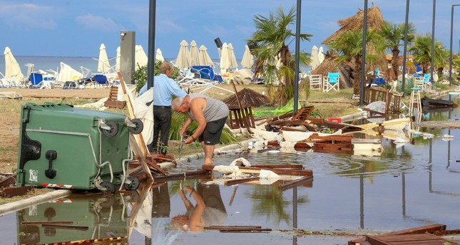 Two men search in debris after a storm at Nea Plagia village in Halkidiki region, northern Greece on Thursday, July 11, 2019. (AP Photo)