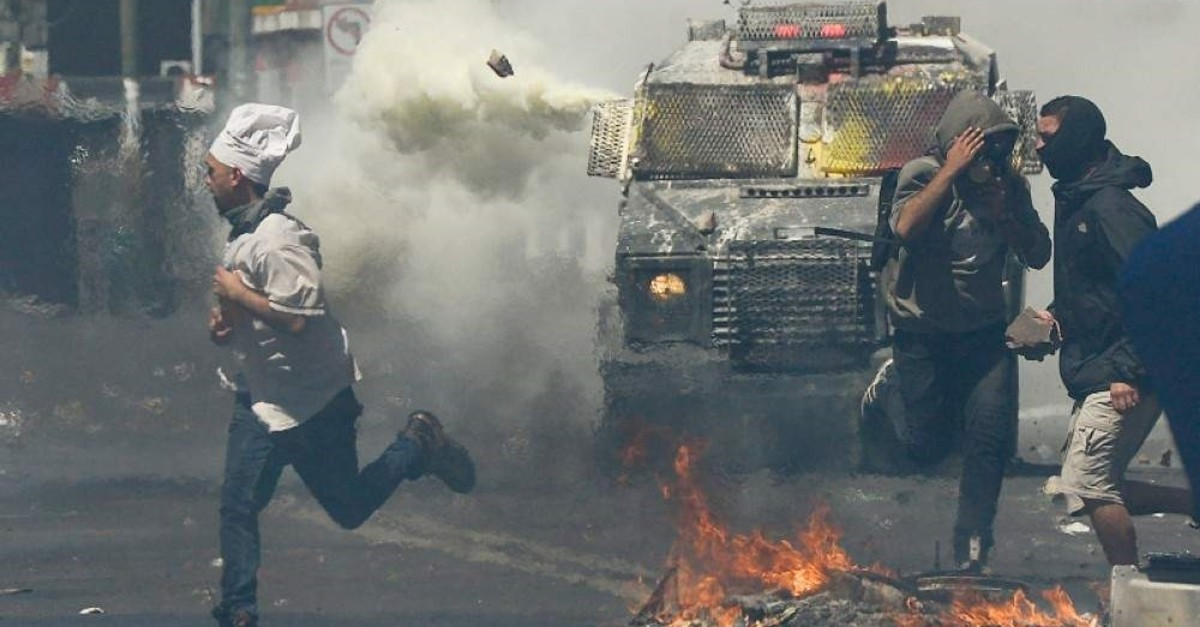 A man wearing a chef's hat runs for cover as anti-government protesters clash with police in Valparaiso, Chile, Thursday, Oct. 24, 2019. (AP Photo)
