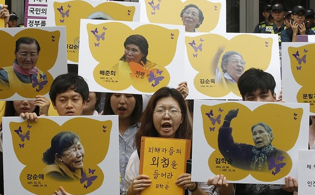 In this July 28, 2016 file photo, protesters hold the portraits of the former sex slaves who were forced to serve for the Japanese military in WWII, during a rally against the Reconciliation and Healing Foundation in Seoul, South Korea. (AP Photo)