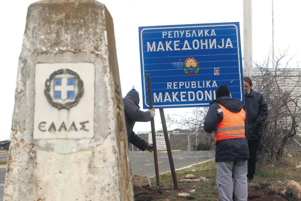 Workers remove a road sign that reads u2018'Republic of Macedonia'' u2013 the other sign reads ,Hellas-Greece, in Greek u2013 on the southern border with Greece, near Gevgelija, Feb. 13, 2019.
