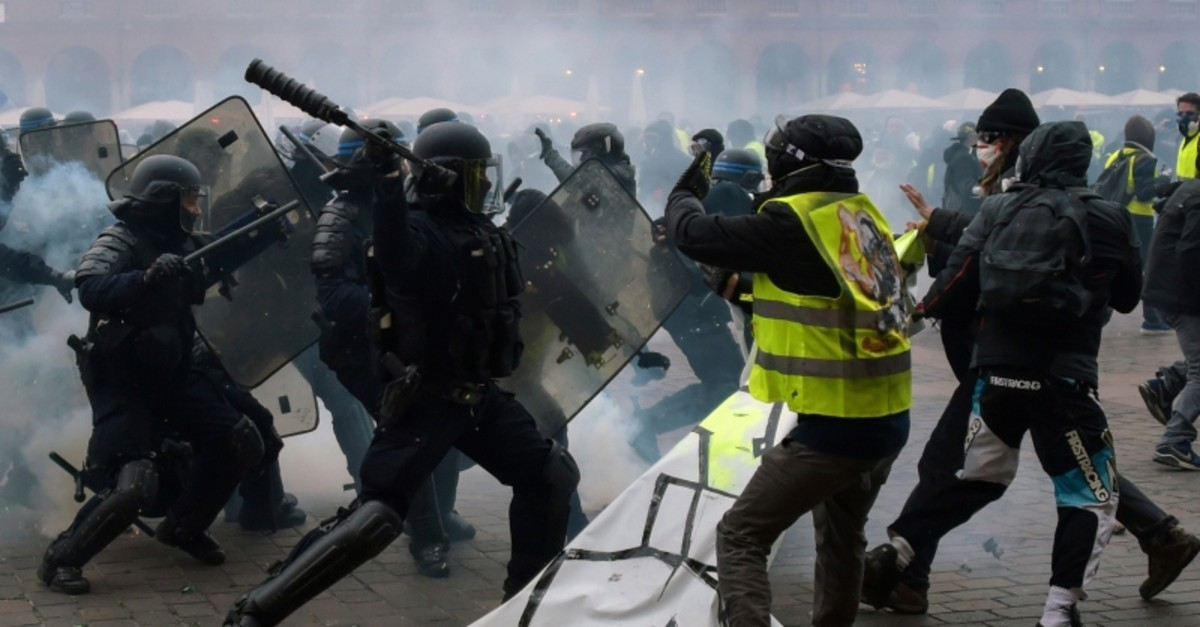 Protestors wearing yellow vests (,gilets jaunes,) clash with police officers during an anti-government demonstration called by the yellow vest movement on January 12, 2019, on the Place du Capitole in Toulouse, southern France. (AFP Photo)