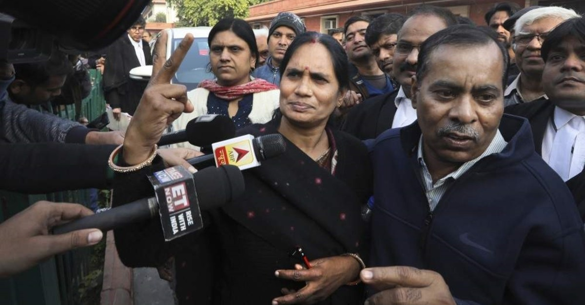Asha Devi, the mother of the victim of the fatal 2012 gang rape, shows a victory sign with her husband Badrinath as they leave Supreme Court, in New Delhi, India, Dec. 18, 2019. (AP Photo)