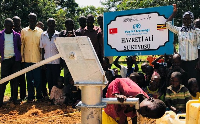 A child drinks from a water pump at a well drilled by the  Turkish charity Vuslat, during its inauguration in 2018 in Uganda.