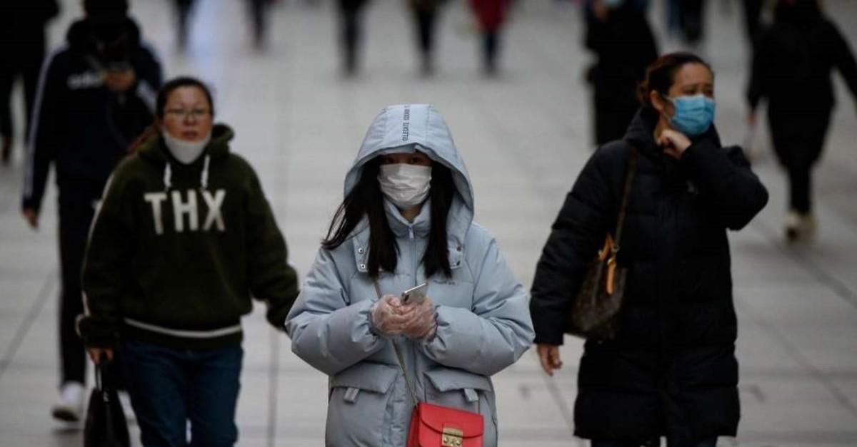 People wearing protective face masks walk along a street, Shanghai, Feb. 19, 2020. (AFP Photo)