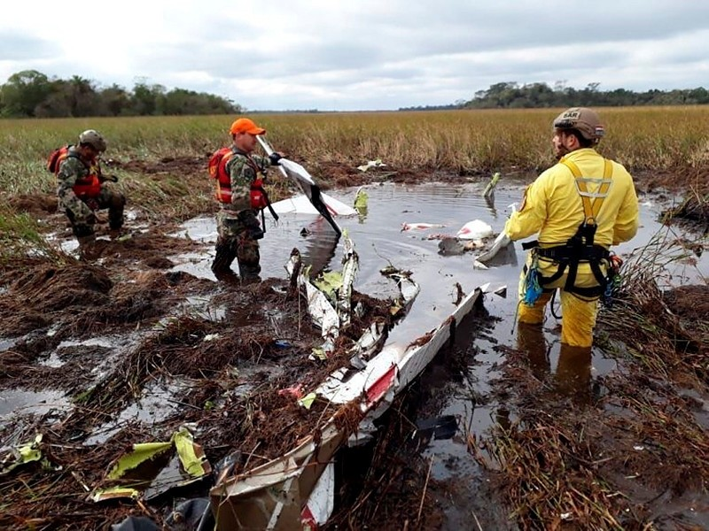Rescue workers search the crash site of a twin-engine Beechcraft Baron in Ayolas, Paraguay, July 26, 2018. (AP Photo)