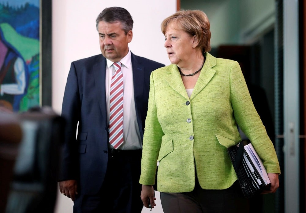 German Chancellor Angela Merkel, right, and German Foreign Minister Sigmar Gabriel, left, arrive for the weekly cabinet meeting at the chancellery in Berlin, Germany. (AP Photo)