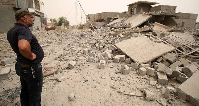 A member of the Iraqi counter terrorism forces inspects collapsed buildings in Fallujah's southern Shuhada neighbourhood after Iraqi gov't forces retook the area from Daesh on June 18, 2016 (AFP Photo)