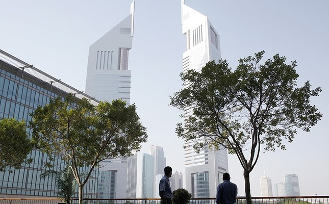 Men stand at the Dubai International Financial Center in Dubai May 5, 2013 (Reuters Photo)