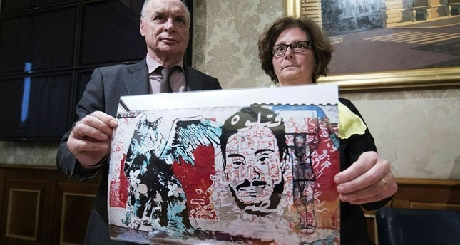 The parents of Giulio Regeni, an Italian graduate student tortured to death in Egypt, shows a pictures of a murales depicting their son. (ANSA via AP)