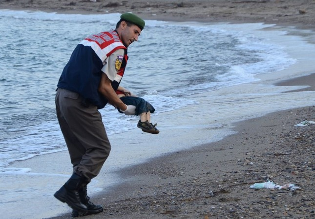 A Turkish police officer carrying the dead body of Aylan Kurdi, a three-year-old migrant child, off the shores of Bodrum in southern Turkey, after a boat carrying refugees sank while attempting to reach the Greek island of Kos, Sept. 2, 2015.
