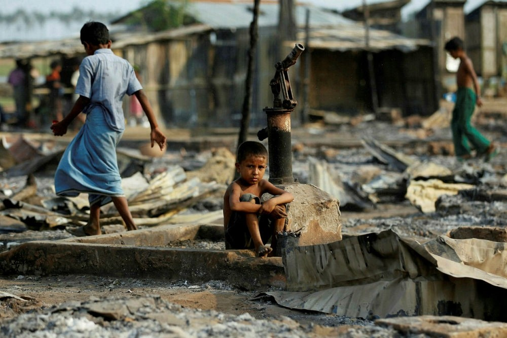 A boy sit in a burnt area after fire destroyed shelters at a camp for internally displaced Rohingya Muslims in the western Rakhine State near Sittwe, Myanmar.